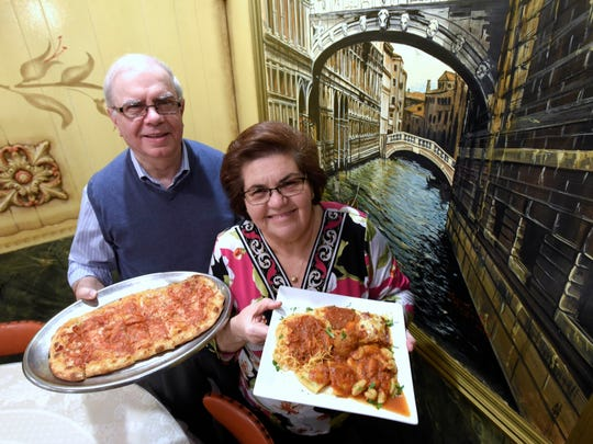 Owners Francesco Improta, 68, and his wife, Lidia, 65, both of Allen Park, hold a plate of tomato bread, left, and the Assorted Pasta Platter near a painting of the Bridge of Syces in Venice, Italy. XXXXThese are images of Vince's Italian Restaurant on Springwells at Homer in Southwest Detroit, Friday afternoon, March 30, 2018. (Todd McInturf, The Detroit News)2018.