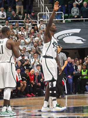 Senior Eron Harris, with his knee in a brace, waves to the crowd in the final seconds of the game.
