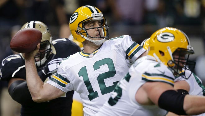 Green Bay Packers quarterback Aaron Rodgers (12) throws a touchdown pass in the first half of an NFL football game against the New Orleans Saints in New Orleans, Sunday, Oct. 26, 2014.