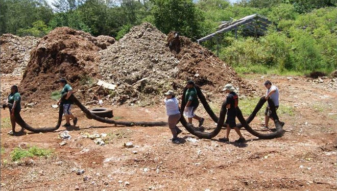 In this file photo, volunteers carry black netting, or sock filled with mulch and other material, to create filters for a project to  prevent soil erosion and sedimentation.