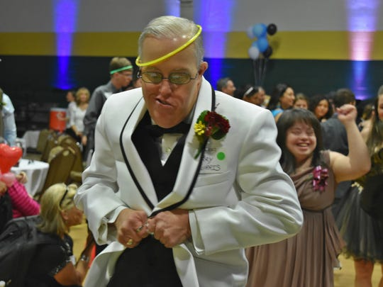 Barry Burris goes to open up his tux jacket to dance up a storm. He was one of about 100 special needs individuals that partied at New Hope Ministries in Naples for Night to Shine on Feb. 10, 2017.