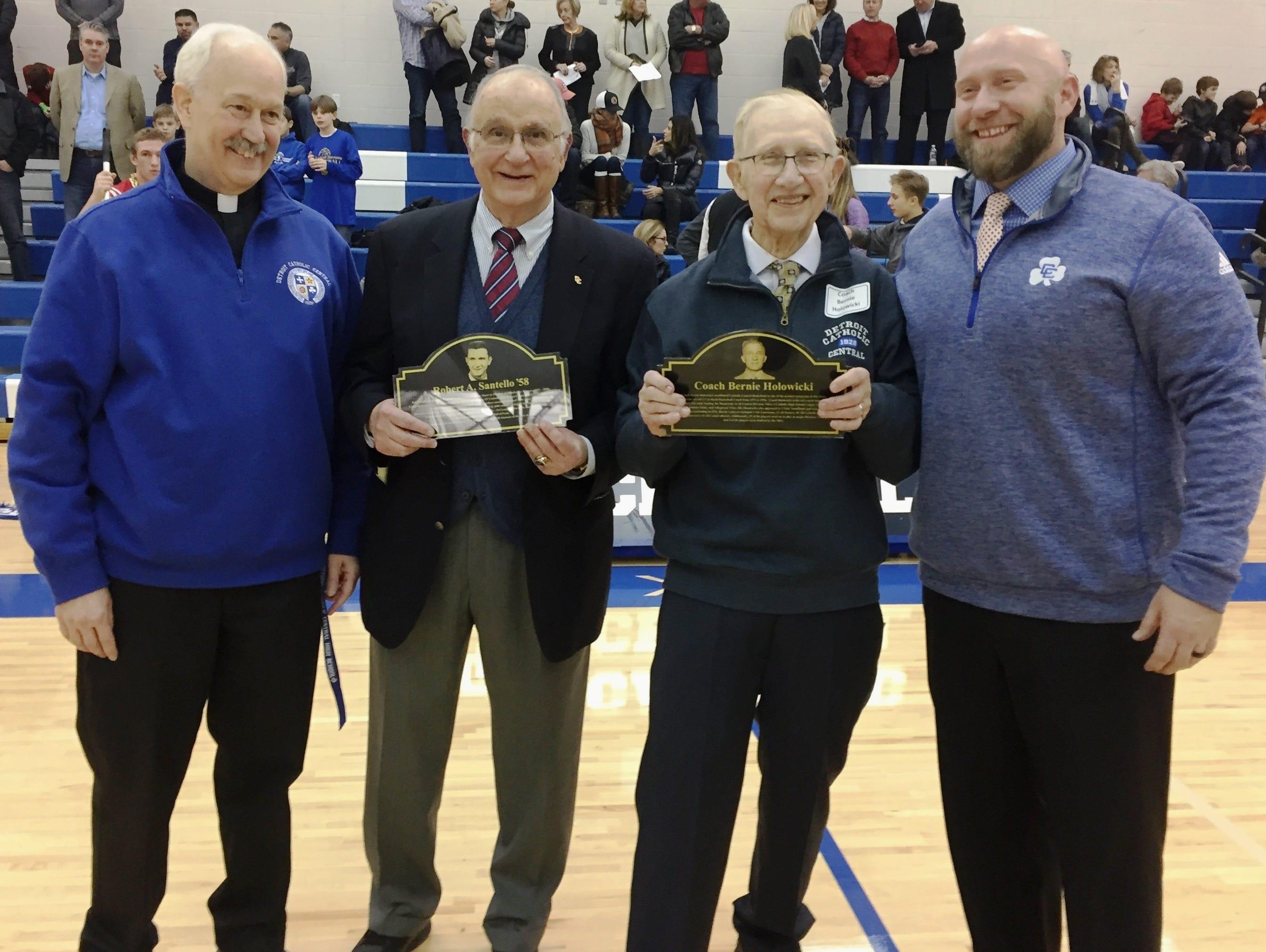Catholic Central principal Fr. Dennis Noelke (far left) and current A.D. Aaron Babicz (far right) honored former A.D. Robert Santello and basketball coach Bernie Holowicki.
