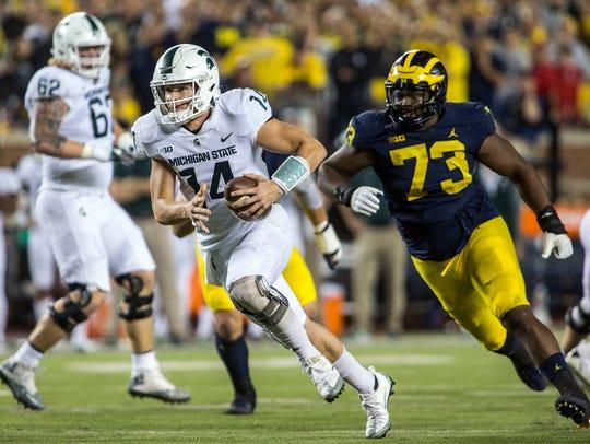 Michigan State quarterback Brian Lewerke (14) rushes