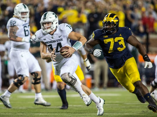 Michigan State quarterback Brian Lewerke (14) rushes ahead of Michigan defensive lineman Maurice Hurst (73) for a touchdown in the first quarter of an NCAA college football game in Ann Arbor, Mich., Saturday, Oct. 7, 2017.