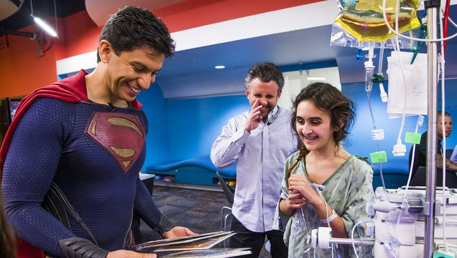 Pierce Mitchell, as Superman, left, meets Marc Wichansky and his daughter Eliana, 12, Paradise Valley, at Phoenix Children's Hospital, Tuesday, March 22, 2016. Mitchell, and two other members of Justice League Arizona, stopped by to promote the new Batman vs Superman film and cheer up the children and their parents in the process.