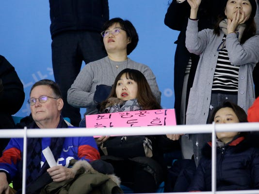 In a photo taken Monday, Feb. 12, 2018, Woo Hee-jun, center, mother of South Korean player Han Dohee, watches the Koreas play a women's hockey game against Sweden at the 2018 Winter Olympics in Gangneung, South Korea. Parents of players at Koreas' joint women's hockey team say they are so proud of their daughters for creating history in inter-Korean relations. (AP Photo/Julio Cortez)