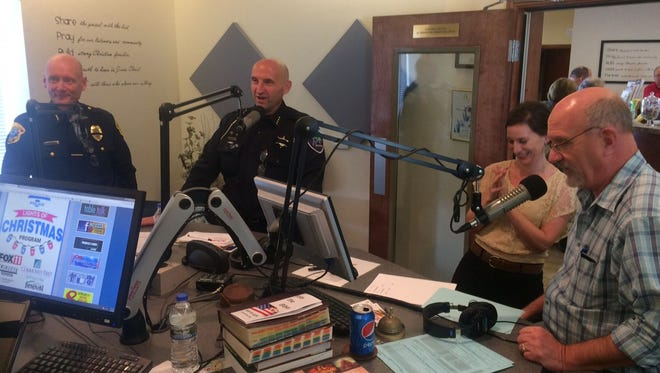 From left, police chiefs Andrew Smith from Green Bay and Todd Thomas from Appleton talk on air with Q90 FM community outreach director Katie Connell and general manager/studio host Mike LeMay on Thursday at the Christian radio station in De Pere.