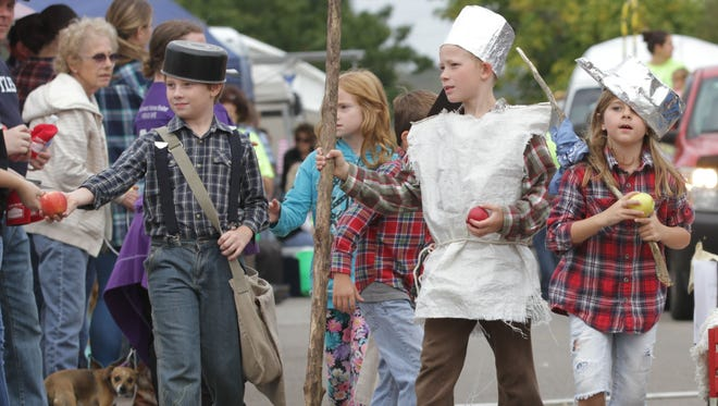 Children from Bultler Elementary School walk down Main Street as part of their town's Apple Festival in 2016. The kids were dressed as the buckeye pioneer, Johnny Appleseed, and were handing out apples.