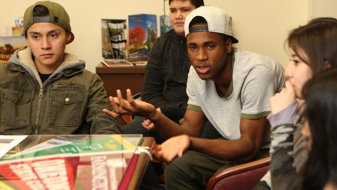 Yunior De La Rosa, chats with a group of English-as-a-new-language students at Peekskill High School.