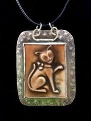 A handmade artisan pottery tile with a cat image is set into sterling silver.