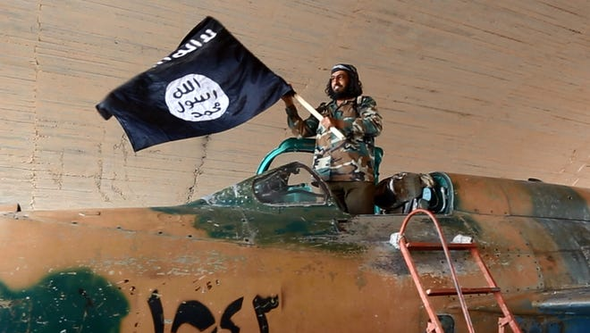 A fighter of the Islamic State group waves their flag from inside a captured government fighter jet following the battle for the Tabqa air base, in Raqqa, Syria.