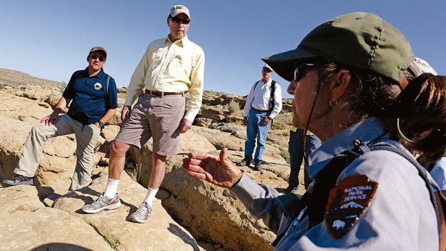 U.S. Department of the Interior Deputy Secretary Mike Connor, left, and New Mexico Sen. Tom Udall listen to Dabney Ford, chief of cultural resources at Chaco, speak Monday at Chaco Culture National Historical Park.