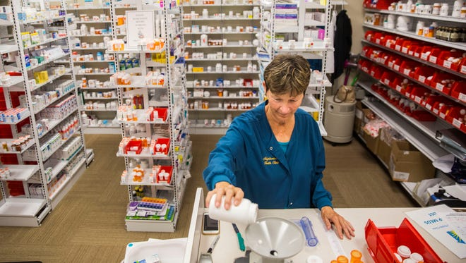 Nancy Windatt fills prescriptions in the pharmacy at the Neighborhood Health Clinic in Naples on Monday, May 14, 2018.