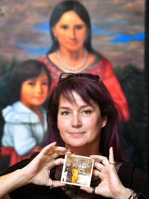 Popular urban fantasy author Sherrilyn Kenyon holds a picture of herself with her parents when she was a little girl. The portrait in the background is of Pocahontas, an ancestor. Friday June 15, 2018, in Franklin, Tenn.