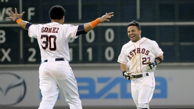 Astros second baseman Jose Altuve, right, celebrates his walk-off RBI single with teammate Carlos Gomez in the ninth inning of Sunday against the Tigers in Houston.