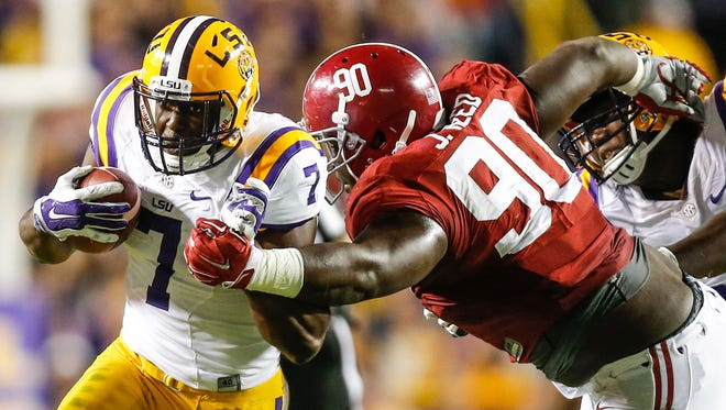 LSU Tigers running back Leonard Fournette (7) is grabbed by Alabama Crimson Tide defensive lineman Jarran Reed (90) during the first quarter of a game at Tiger Stadium.