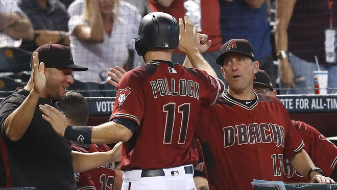 The Diamondbacks' A.J. Pollock (11) high-fives manager Torey Lovullo (17) and David Peralta (L) after scoring on a two-run home run by Nick Ahmed during the fourth inning against the Padres at Chase Field in Phoenix, Ariz. on April 22, 2018.