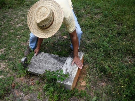 Lawrence Joyce rights a headstone that was toppled