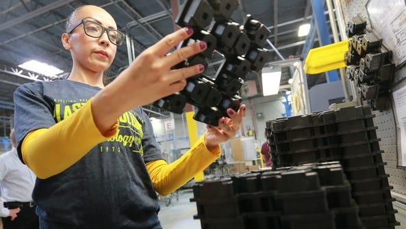 Judith Verdim inspects a plastic molding before placing