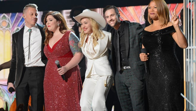 Macklemore, left,  Mary Lambert, Madonna, Ryan Lewis and Queen Latifa celebrate the marriages of 33 couples during the 2014 Grammy Awards in Los Angeles.
