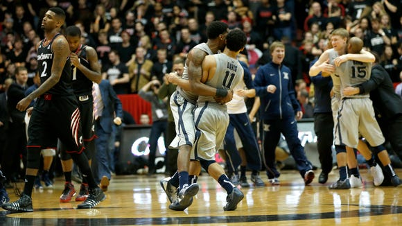 Xavier guards Dee Davis (11) and Remy Abell embrace