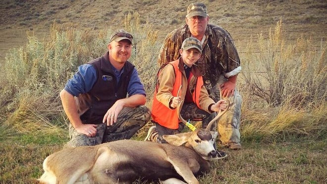 Dane Hager with his deer. His father, Justin, is on the left and his grandfather, Tim, is on the right.