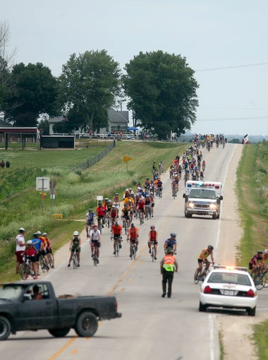 Riders pedal up a hill as an ambulance passes by on Thursday, July 24, 2014, just outside Waverly, Iowa.