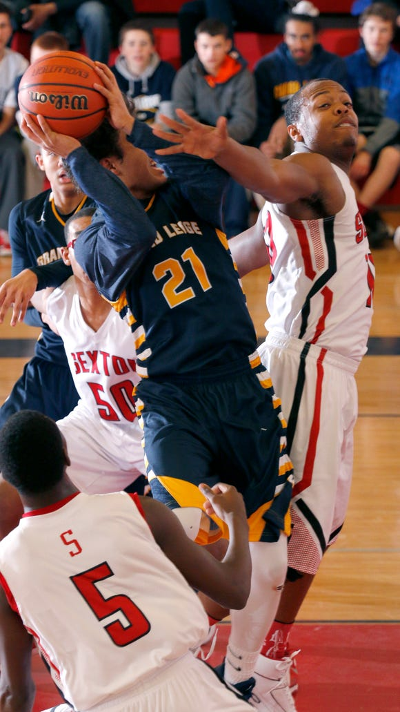 Grand Ledge's Malek Adams (21) puts up a driving shot against Sexton's Avonte Bell, right, and Ardis Davis (5) Friday. Grand Ledge won 70-59.