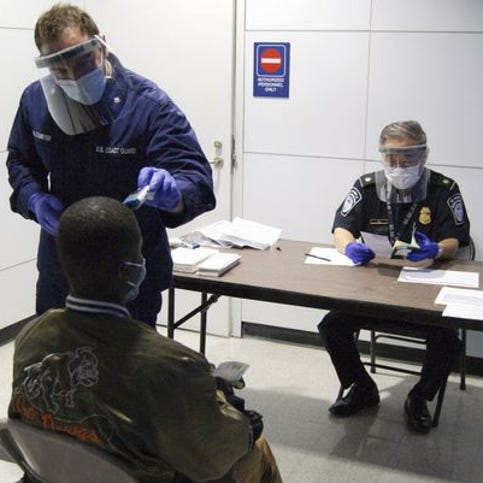 In this Thursday, Oct. 16, 2014, file photo released by U.S. Customs and Border Protection, U.S. Coast Guard Health Technician Nathan Wallenmeyer, left, and CBP supervisor Sam Ko, right, conduct prescreening measures on a passenger who has arrived from Sierra Leone at O'Hare International Airport's Terminal 5 in Chicago.