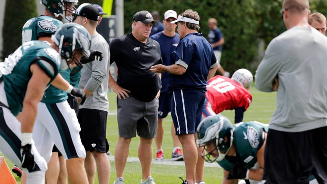 Eagles head coach Chip Kelly (center left) talks with Patriots head coach Bill Belichick during a joint practice in Foxborough, Mass., on Tuesday.