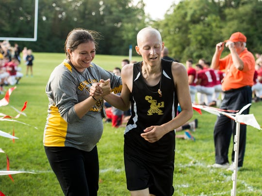 Tommy Laudani is congratulated by Delone Catholic assistant coach Ashley Zinn after Laudani completed his first 5K race since being diagnosed with cancer in November 2016.