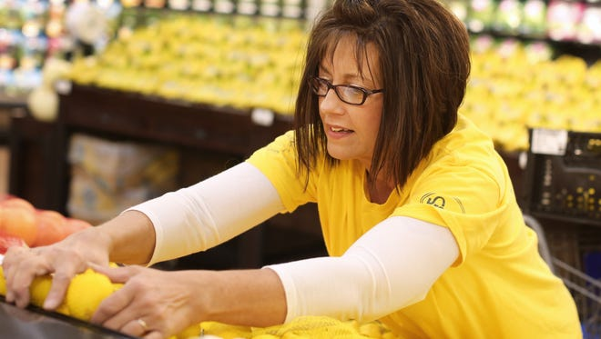 Workers, like Barb Lane, were busy putting on finishing touches at the new Oakley Kroger Marketplace.