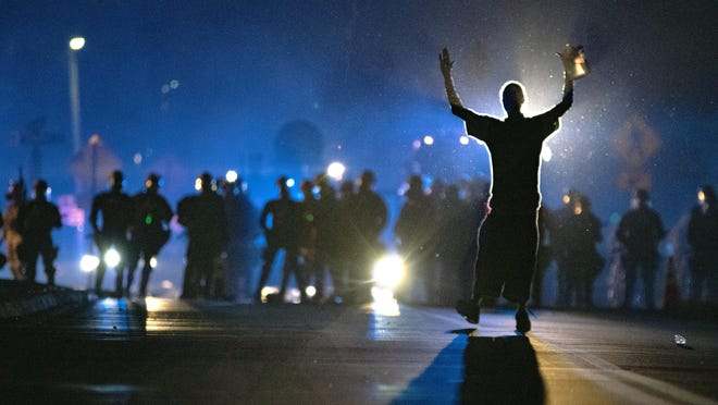 A protester moves towards a police line in front of the Arkansas State Capitol building in Little Rock on Monday, June 1, 2020.