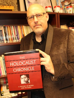 Troy Montgomery Professor Dan Puckett holds a detailed book about the Holocaust.