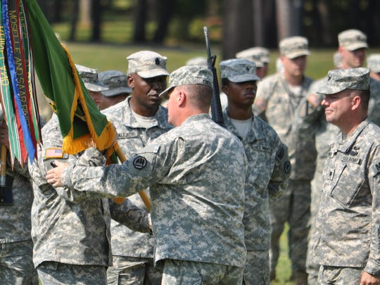 Maj. Gen. Glenn H. Curtis (right center), adjutant general of the Louisiana National Guard, gives command of the 773rd Military Police Battalion to Lt. Col. Richard Douget (left) Saturday during a ceremony at Camp Beauregard.