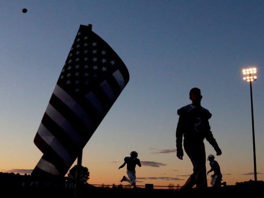 American flags line parts of the field as players warm up before the Stratford vs. Auburndale high school football game at Auburndale High School in Auburndale, Wis. on Friday, September 29, 2017.
