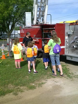 Children listen to a firefighter describe his engine during a recent event.