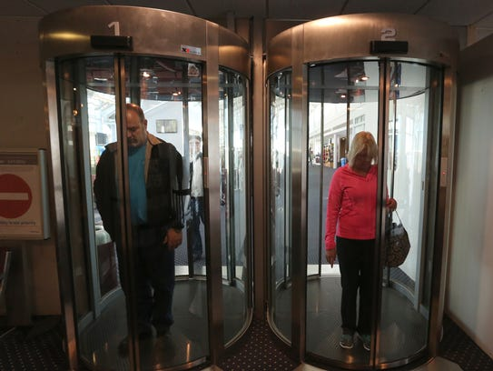 Two passengers wait for circular glass doors to open