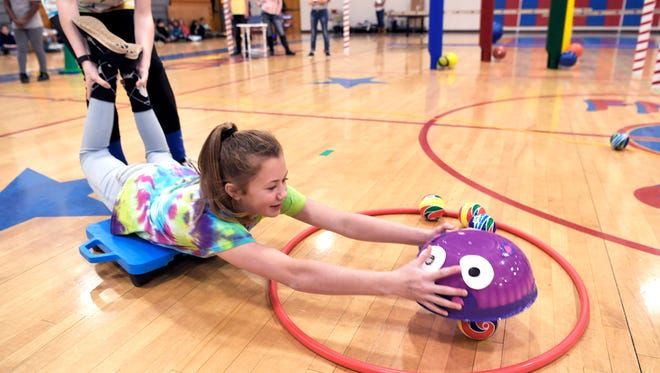 Freedom Middle School students like Emily Grace Carter practice at their fitness stations in the school's gym Wednesday, Dec. 6, 2017. The fitness stations are part of the TECHFIT program, which combines physical fitness with programming/coding and engineering. The students will compete at Purdue University in a TECHFIT competition.