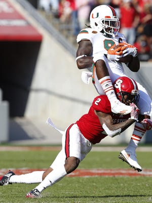 N.C. State cornerback Mike Stevens tackles Miami wide receiver Malcolm Lewis.