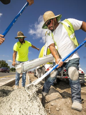 Steven Goodwin and Juan Castro, both with DAB Constructors, pour concrete for a curb at the intersection of State Road 200 and Interstate 75 on Thursday. The Marion County Transportation Planning Organization is putting together a long-range priority list of transportation projects for the next 25 years.