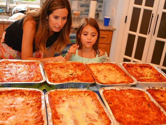 Rianna and Clara Drew Day look over pans of lasagna,