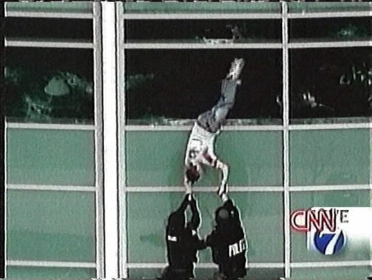 Severely wounded patrick ireland being helped out a window by swat