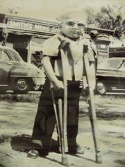 Rich Willett as a child, standing with his crutches.