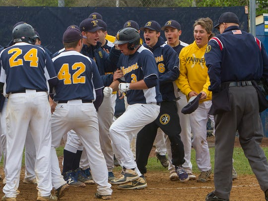 Teammates swarm Toms River North's Jeff Ciervo as he crosses the plate after hitting a two run homer in the fifth inning. Barnegat Baseball vs Toms River North in Toms River, NJ on April 7, 2016
