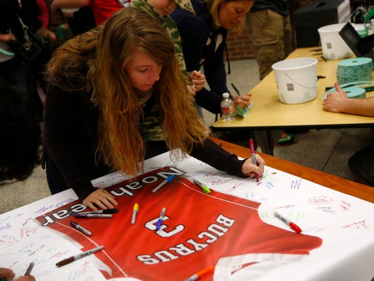 Mykala Houseburg, 17, signs a poster in tribute to