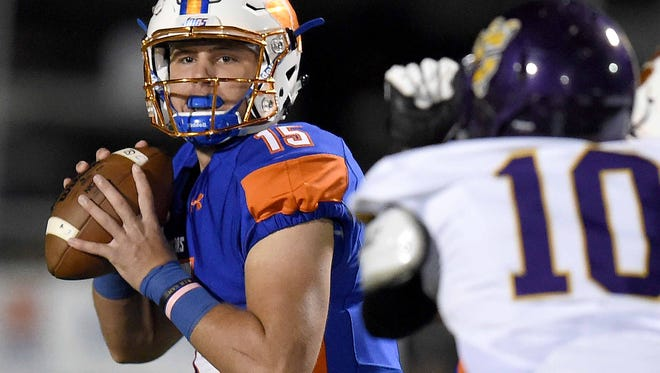 Madison Central quarterback Jack Walker (15) looks down field for a receiver against Columbus.