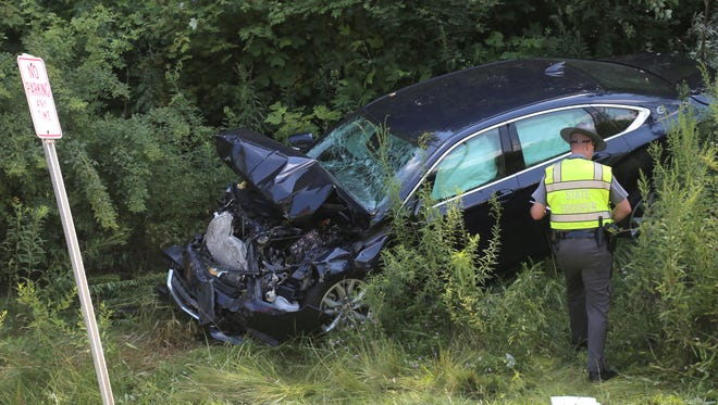 An Ohio Highway Trooper looks over a vehicle that was involved in a head-on crash on Cook Road in Mifflin Township on Wednesday, Aug. 2.