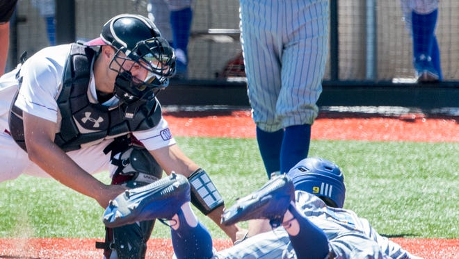 New Mexico State catcher Mason Fishback blocks the plate and puts the tag on Bakersfield's Ryan Grotjohn Saturday morning at Presley Askew Field.