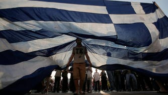 Protesters hold a giant a Greek flag during a rally in Athens, Greece, 29 June 2015. Greek voters will decide in a referendum on July 5th whether their government should accept an economic reform package put forth by Greece's international creditors.